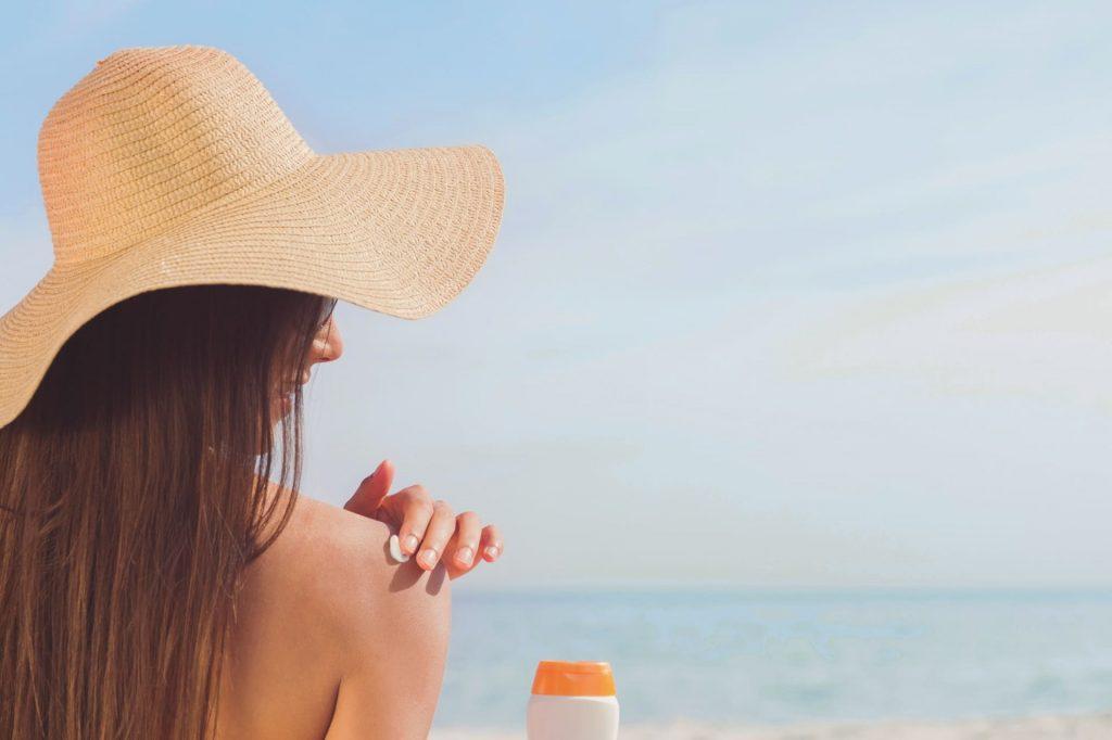 Mulher passando filtro solar nos ombros